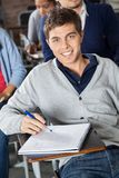 Man With Exam Paper Sitting At Desk In Classroom Royalty Free Stock Images