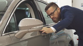 Man examines the car at the dealership. Attractive caucasian man examining new car at the dealership. Bearded male customer touching the door of the vehicle stock video