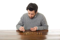 Numismatist. Man examines coins on a desk, isolated Royalty Free Stock Image