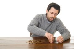 Numismatist. Man examines coins on a desk, isolated Stock Photos