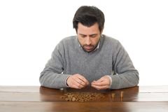 Numismatist. Man examines coins on a desk, isolated Royalty Free Stock Photo