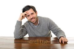 Numismatist. Man examines coins on a desk, isolated Royalty Free Stock Photography