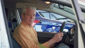 Man examines interior of the car. Gray senior man examining the interior of the car. Aged male customer touching the center console of the vehicle. Attractive Royalty Free Stock Photos