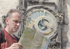 Man examines the map on background of historical medieval astronomical Clock on the Old Stock Images