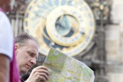 Man examines the map on background of historical medieval astronomical Clock on the Old Town Hall in Prague, Czech Republic Stock Images