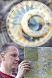 Man examines the map on background of historical medieval astronomical Clock on the Old Town Hall in Prague, Czech Republic Royalty Free Stock Photos