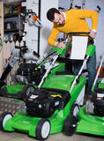 Man examines a modern lawnmower Royalty Free Stock Photo