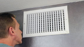 Man Examining an Air Vent. Mature male looking inside an upper wall white grid air duct on a gray wall near a white ceiling. A guy examining a heating and stock video