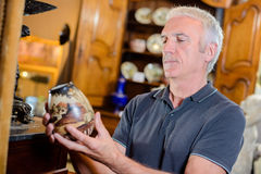 Man examining antique pot Royalty Free Stock Image
