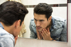 Man Examining Face in Reflection of Mirror Royalty Free Stock Images