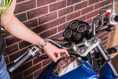 Man Examining Gas Gauge on Tank of Blue Motorcycle Stock Photography