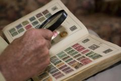 Man Examining An Old Stamp Book. Closeup of a senior man's hand looks at stamp collection with magnifying glass Royalty Free Stock Images
