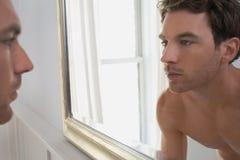 Man Examining Reflection In Mirror Stock Photo