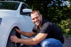 Man examining tires at his new car stock photos