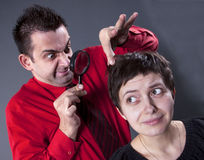 Man examining woman's hair Royalty Free Stock Photography