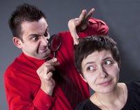 Man examining woman's hair Royalty Free Stock Photography