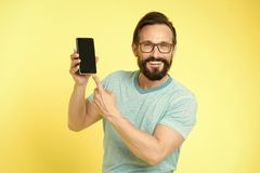 Man excited about new mobile opportunities. Guy eyeglasses cheerful pointing at smartphone. Man happy user interact. Application for smartphone. Guy bearded stock photo