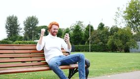 Man Excited for Successs, Using Smartphone, Sitting on Bench stock video footage