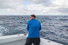 A man in excitement with a spinning in his hands pulls fish from the ocean from the side of the boat.. fishing in Florida. USA. royalty free stock photos