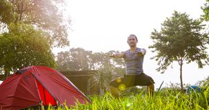 A man exercise and Athlete Warming Up in morning near tent on camping trip on the mountain.  stock photos