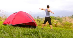 A man exercise and Athlete Warming Up in morning near tent on camping trip on the mountain royalty free stock photography