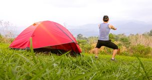 A man exercise and Athlete Warming Up in morning near tent on camping trip on the mountain royalty free stock photos