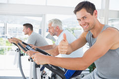 Man on exercise bike gesturing thumbs up Royalty Free Stock Image