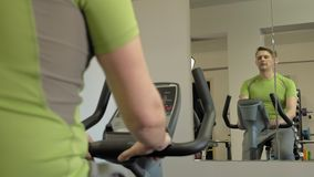 Man on exercise bike in the gym. Healthy lifestyle concept. Handsome mature man in a green t-shirt on a stationary bike in a gym. Healthy lifestyle concept stock video