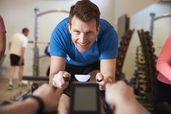 Man on exercise bike in a spinning class at a gym, close up Royalty Free Stock Photos
