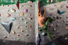 Man exercise bouldering and climbing indoor. Muscular and fit topless man exercise bouldering and climbing indoor at artificial wall Royalty Free Stock Images