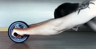 Man on an Exercise Wheel. Getting in shape with an exercise wheel Royalty Free Stock Photo