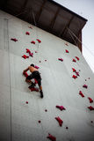 Man exercises on indoor rock climber Royalty Free Stock Image