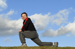 Man exercising. A forties man is doing some stretching on the grass outdoors against a backdrop of a blue cloudy sky Royalty Free Stock Image