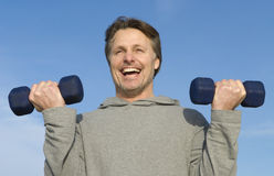 Man exercising. A happy forties man is performing dumbell curls to strengthen his arms Stock Photos