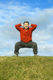 Man exercising. A handsome forties man is performing some squats in a grass field Royalty Free Stock Images