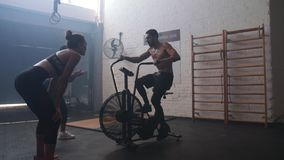 Man exercising on air bike in gym with friends stock footage