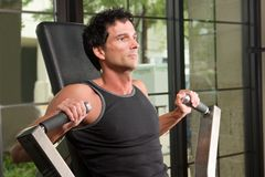 Man Exercising Arm Muscles. Man exercising his arm muscles on an exercise machine in a fitness center Royalty Free Stock Photography