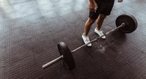 Man exercising with barbell at gym. High angle view of man feet with heavy weights on gym floor Royalty Free Stock Image