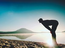 Man exercising on beach.  Silhouette of active man exercising  and stretching at lake Royalty Free Stock Image