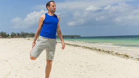 Man exercising on beach. He is stretching. Stock Images