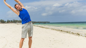 Man exercising on beach. He is stretching. Royalty Free Stock Images