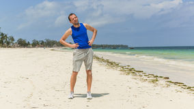 Man exercising on beach. He is stretching. Stock Photography
