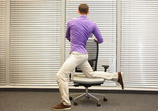 Man exercising on chair in office Royalty Free Stock Photography