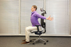 Man exercising on chair in office, healthy lifestyle. Profile view royalty free stock photo
