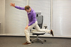 Man exercising on chair in office, healthy lifestyle Stock Image