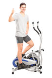 Man exercising on a cross trainer machine and giving thumb up. Full length portrait of a young man exercising on a cross trainer machine and giving thumb up Royalty Free Stock Photo