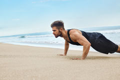 Man Exercising, Doing Push Up Exercises On Beach. Fitness Workout. Workout Exercise. Closeup Of Healthy Handsome Active Man With Fit Muscular Body Doing Push Ups Stock Image
