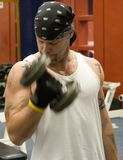 Man exercising with dumbbell. Half body portrait of young man with bandanna exercising with dumbbell in gym Royalty Free Stock Photo