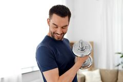 Man exercising with dumbbell at home stock photography