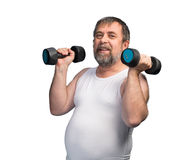 Man exercising with dumbbells. Middle-aged man with a paunch exercising with dumbbells isolated on white background Stock Photo
